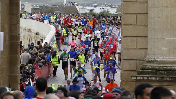 Los participantes a su paso por la Puerta del Puente