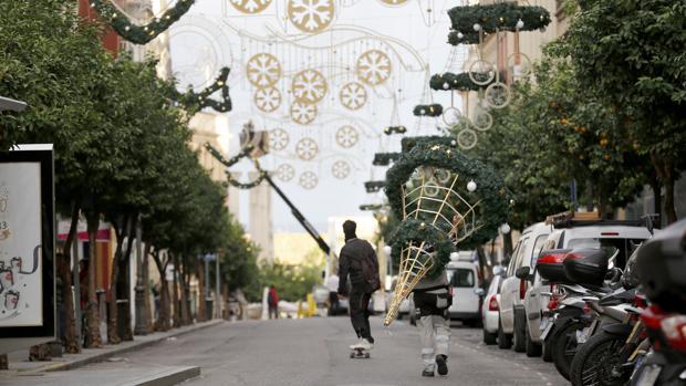 Un operario tarnsporta un decorado navideño por la calle Claudio Marcelo