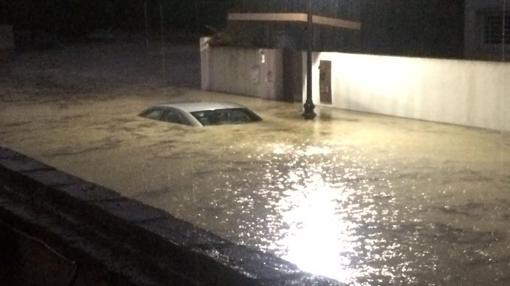 Un coche hundido bajo el agua tras el paso de la tormenta en el término de Aljaraque