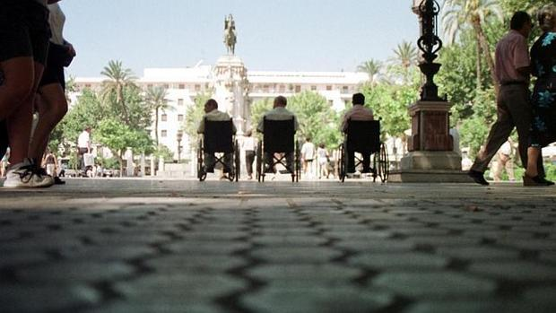 Tres personas en silla de ruedas en la plaza Nueva de Sevilla