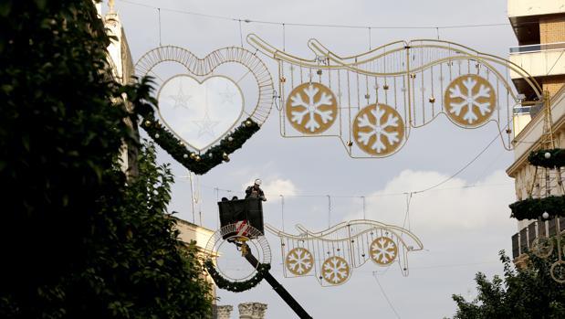 Un operario ultima los detalles en las luces de Navidad