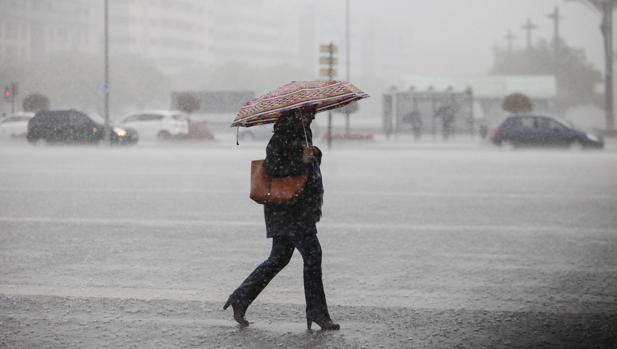 Una viandante cruza la plaza de las Tres Culturas en plena lluvia