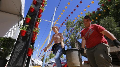 Dos personas entran con una maceta en una caseta de la Feria