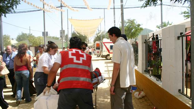 Personal de la Cruz Roja atiende a una persona herida en la Feria
