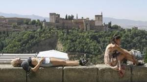 Dos turistas toman en sol en Granada aprovechando las altas temperaturas