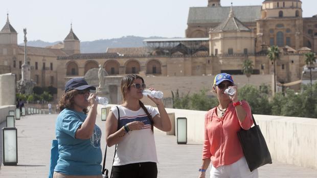 Tres jóvenes se refrescan en el Puente Romano