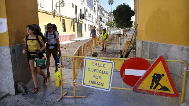 Turistas pasean junto la calle Caballerizas Reales, cortada por obras