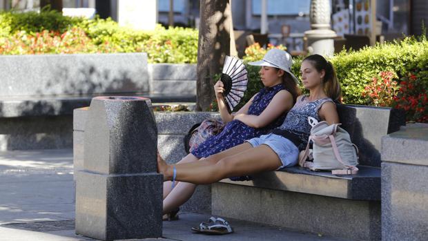 Dos personas se refugian del calor a la sombra en la Plaza de las Tendillas