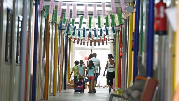 Un grupo de niños camina con sus mochilas por el pasillo de un colegio
