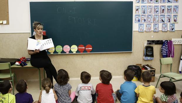 Un grupo de niños atiende a la profesora en un aula