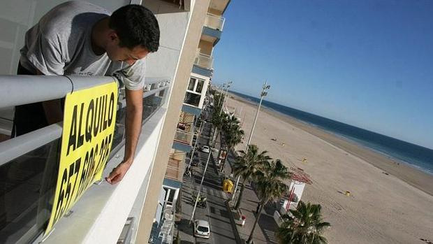 Un hombre coloca el cartel de alquiler en un piso en la playa