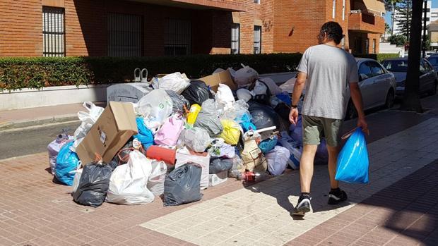 Un vecino se dispone a tirar la basura, ayer en Rota