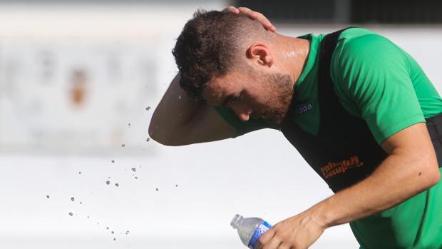 Javi Galán, extremo del Córdoba CF, se moja la cabeza con agua en un entrenamiento