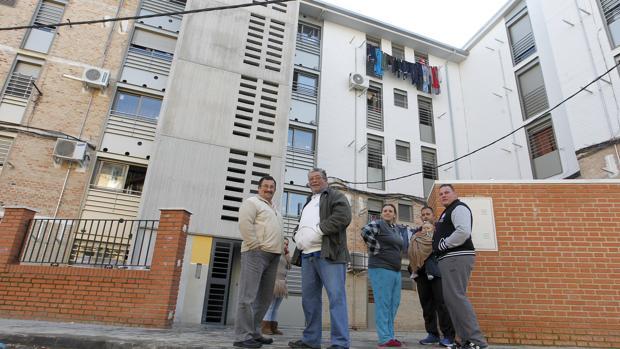Vecinos ante un bloque de pisos de la calle Loja, en el Distrito Sur