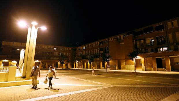 Dos personas pasan por la Plaza Patio La Voz del Pueblo de Las Moreras donde se produjo el apuñalamiento