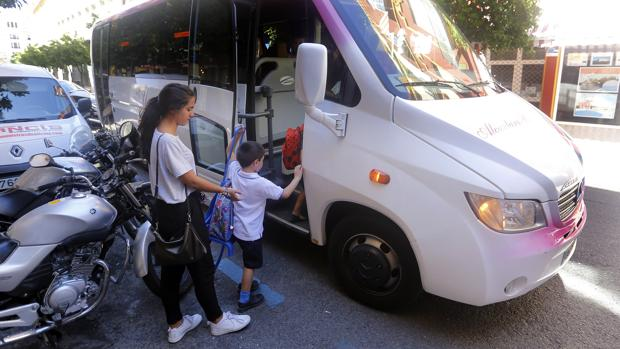 Un grupo de niños sube a un microbús escolar