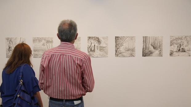 Dos de los primeros visitantes observan unos dibujos
