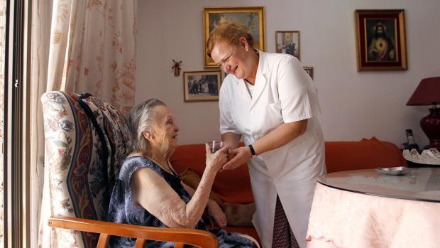Una asistente prestando su ayuda a una cordobesa en situación de dependencia