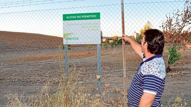 Un vecino señala el cartel del depíosito de uranio