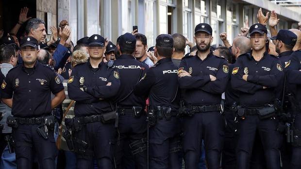 A la izquierda, el lider de los populares en Cataluña, visita a los policías acosados en Barcelona