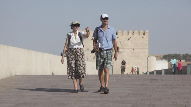 Una pareja de turistas paseando por el Puente Romano