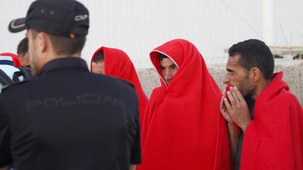 Unos inmigrantes aguardan en el puerto tras llegar a las costas andaluzas