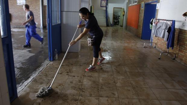 Una mujer limpia el barro en unas viviendas de la barriada de La Asunción de Jerez de la Frontera
