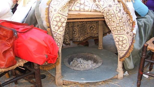 Un brasero de picón bajo una mesa camilla