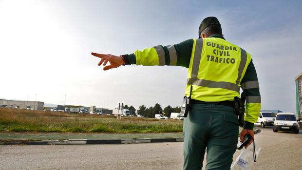 Un agente de tráfico regula los vehículos en una zona de acceso
