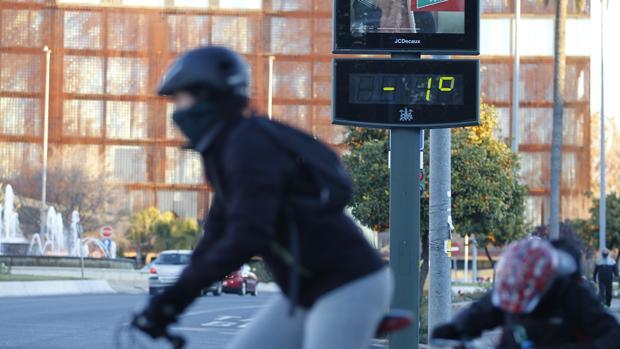 Un ciclista bien abrigado cruza la avenida Vallellano de Córdoba con un termómetro en negativo