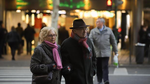 Dos personas pasean protegidas contra el frío