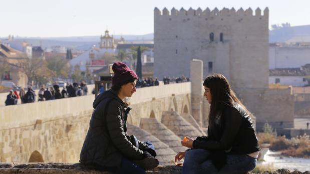 Dos jóvenes descansan al sol, con la Calahorra y el Puente Romano al fondo