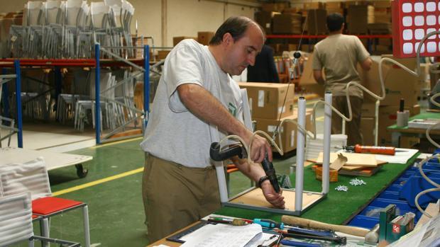 Un trabajador monta una silla en una fábrica de muebles