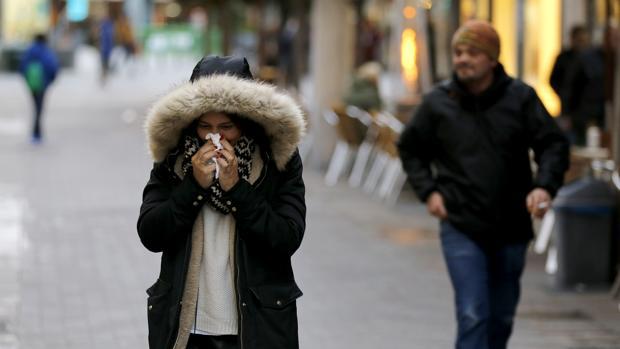 Una mujer se suena la nariz en el Centro de la ciudad