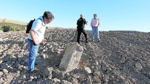 Dos arqueólogos y un policía en una zona del yacimiento de Ategua