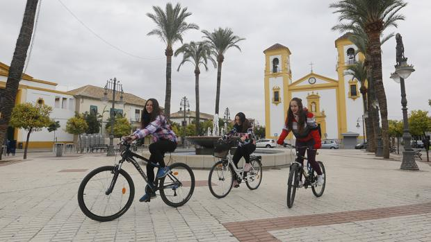 Tres jóvenes en bicicleta por la plaza de Cañero