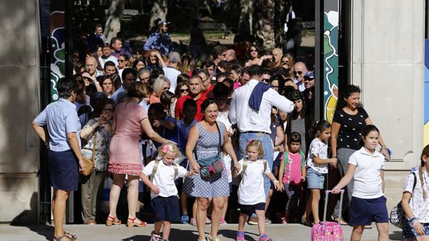 Padres, madres y alumnos en la puerta del colegio