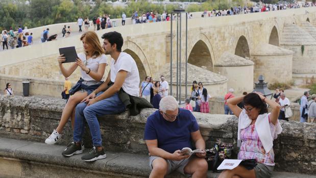 Turistas en Córdoba con el Puente Romano al fondo