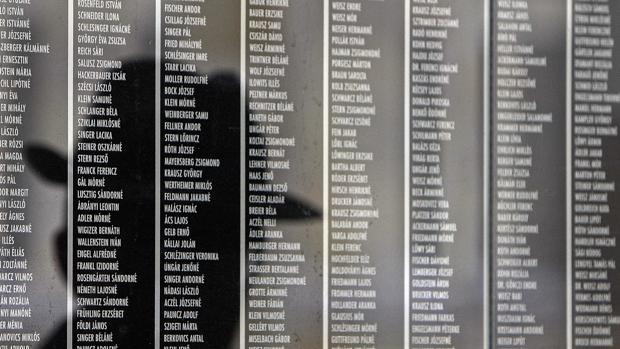 Un húngaro se refleja en el muro que contiene a las víctimas de judíos de este país en el Holocausto nazi