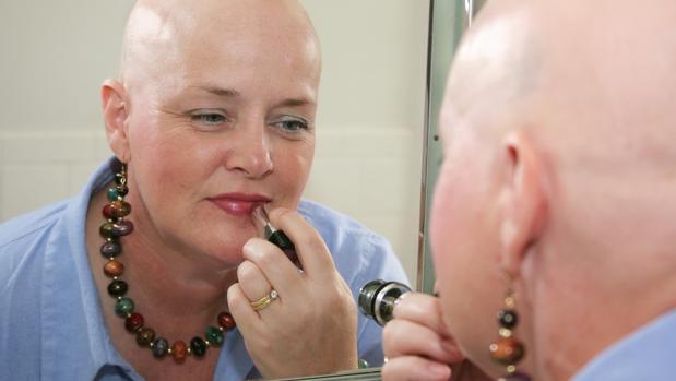 Una paciente oncológica se maquilla frente al espejo