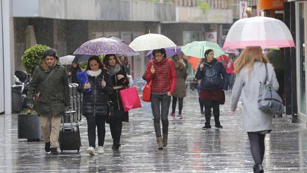 Varias personas pasean por el Centro de Córdoba con paraguas, este domingo