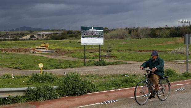 Un ciclista pasa junto al cartel que anuncia las obras del Parque de Levante