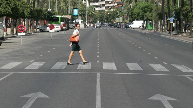 Una viadante cruza el Paseo de la Victoria de Córdoba