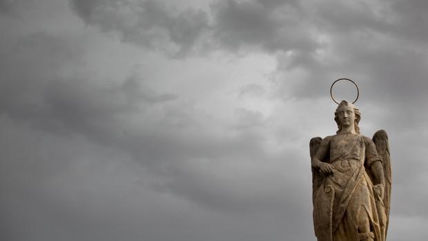 El Arcángel San Rafael en primer plano; detrás, el cielo tormentoso