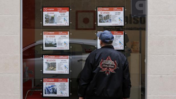 Un hombre mira los carteles de pisos en venta en una inmobiliaria del Centro de Córdoba
