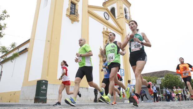 Varios corredores pasan por la plaza y la iglesia de Cañero