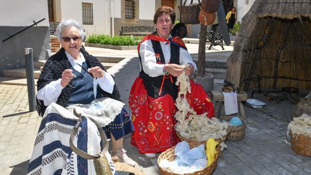Dos mujeres trenzan lana de oveja en una calle de Villaralto