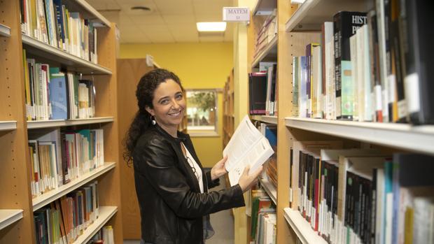 Bárbara Luque sostiene un libro en la biblioteca