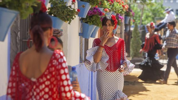 Una joven fuma ante una caseta del recinto ferial de Córdoba