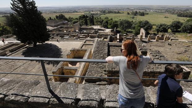 Una joven mira los restos arqueológicos apoyada en una barandilla